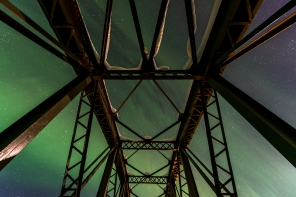 Aurora seen through the Kalixfors bridge. The Beehive Cluster is visible between the beams.