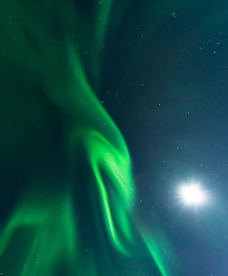 Auroral corona shining bright next to the moon.